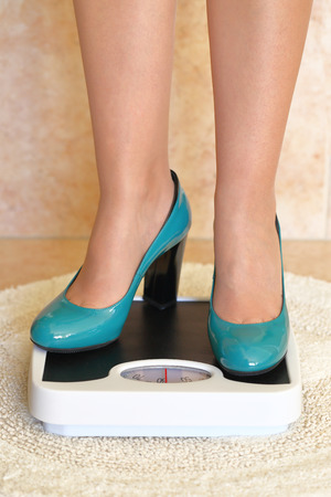 high scale: Womans feet in high heels on bathroom scale Stock Photo