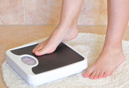 bathroom woman: Womans feet on bathroom scale. Diet concept