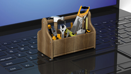 toolkit: Toolkit with various tools on laptops keyboard Stock Photo