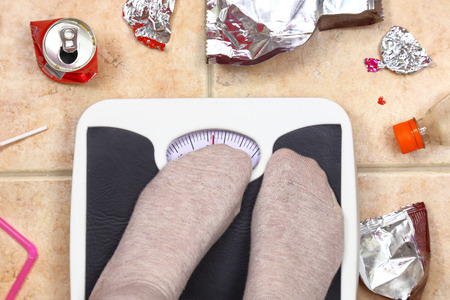 dietitian: Feet on bathroom scale with junk food garbage around Stock Photo