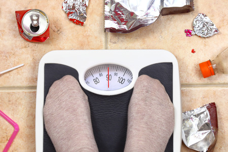 Feet on bathroom scale with junk food garbage around Stock Photo