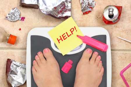obesity: Feet on bathroom scale with word Help and junk food garbage