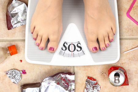 Feet on bathroom scale with word SOS and junk food garbage Stock Photo