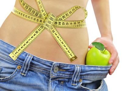 Womans fit belly with measuring tape,apple and oversized jeans, isolated on white Stock Photo