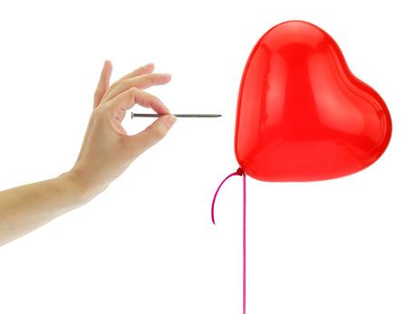 corazon roto: Nail punto de reventar un globo de corazón aislado en blanco Foto de archivo