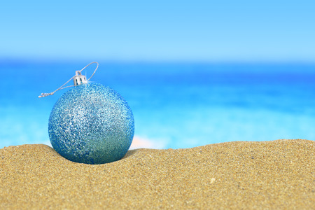 Christmas ball on sandy beach Imagens