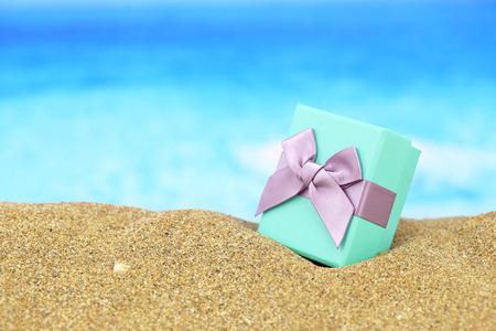 cajas navideñas: Caja de regalo con arco en la arena