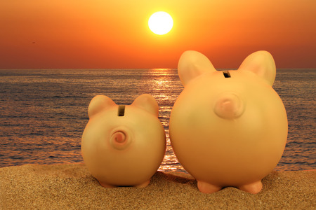 Two piggy banks on the beach looking to the sunset Stock Photo