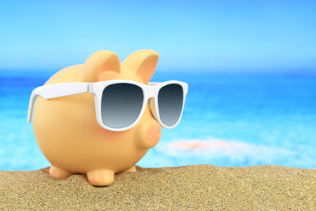 budget crisis: Summer piggy bank with sunglasses on beach