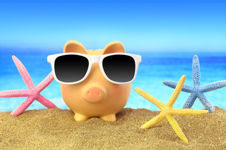 budget crisis: Summer piggy bank with sunglasses and starfishes on beach