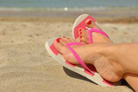 sandalia: Womans pies con chanclas en la arena