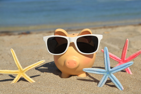 holiday profits: Summer piggy bank with sunglasses on the sand