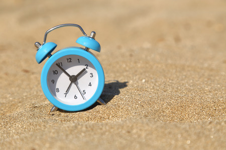 Vacation time. Alarm clock on the sand photo