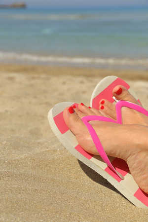 flip flops: Womans feet with flip flops on the sand