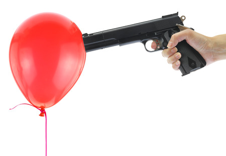 aggressor: Hand holding at gunpoint a red balloon isolated on white