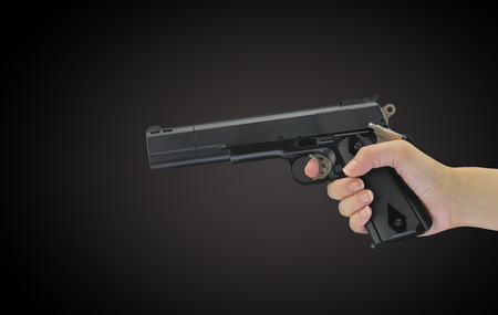 aggressor: Hand holding gun isolated on black