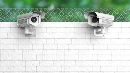 chainlink fence: Security surveillance camera on white brick wall with chain-link fence Stock Photo
