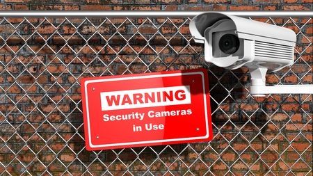chainlink fence: Security surveillance camera on chain-link fence with warning sign Stock Photo
