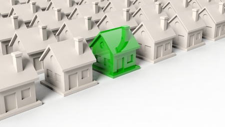 standing out: House models rows with one green standing out with copy-space Stock Photo