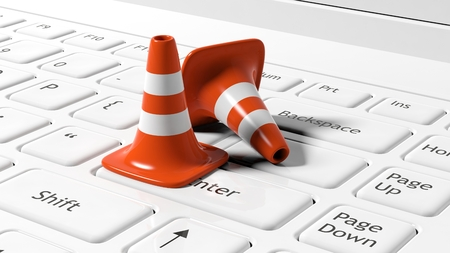 under construction symbol: Orange traffic cones on white laptop keyboard Stock Photo