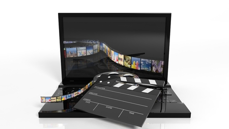 Clapperboard and film reel on black laptops keyboard isolated on white