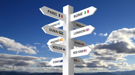 White signpost with various city names on blue sky background Reklamní fotografie