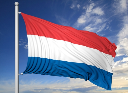 netherlands flag: Waving flag of Netherlands on flagpole, on blue sky background. Stock Photo