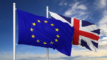 Waving flags of EU and UK on flagpole, on blue sky background. Stock Photo