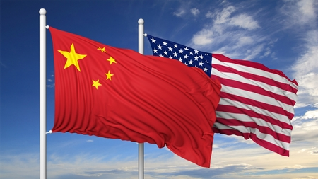 summits: Waving flags of China and USA on flagpole, on blue sky background.