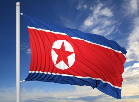 Waving flag of North Korea on flagpole, on blue sky background.