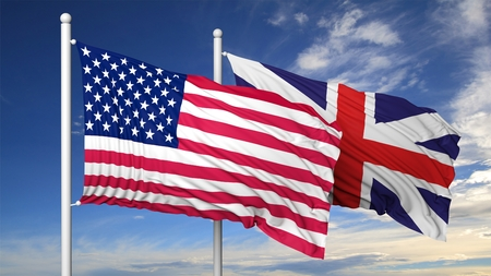 international business agreement: Waving flags of USA and UK on flagpole, on blue sky background.