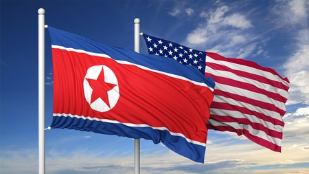 Waving flags of North Korea and USA on flagpole, on blue sky background.