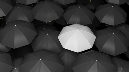 business challenge: Classic large black umbrellas tops with one white standing out. Stock Photo