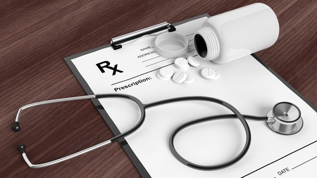form: Blank prescription form with bottle of pills and stethoscope, on wooden desktop.