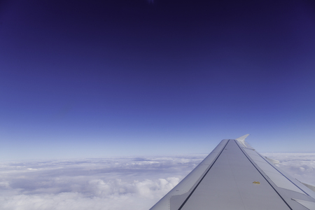 troposphere: Wing of airplane above the clouds in the sky, view from window.