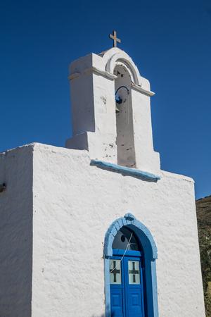 puertas antiguas: Pequeña iglesia de edad con campanario en el cielo azul