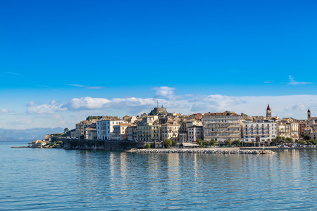 city buildings: Corfu island cityscape from the sea with blue waters and sky. Stock Photo