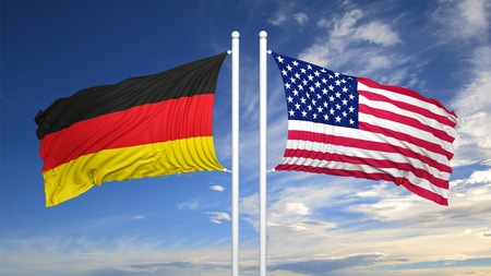 hostility: German and American flags against of blue sky Stock Photo