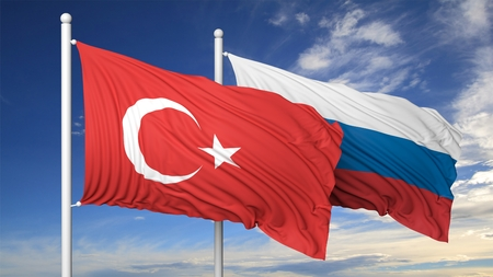 coalition: Turkish and Russian flags against of blue sky.