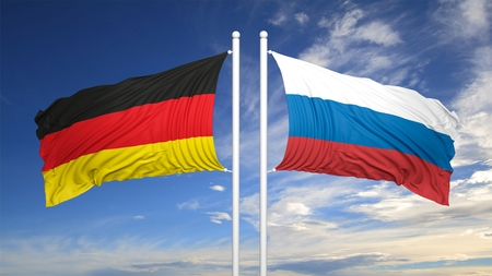 coalition: German and Russian flags against of blue sky
