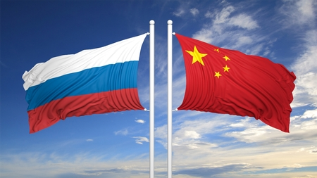 hostility: Russian and Chinese flags against of blue sky Stock Photo