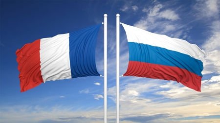 hostility: French and Russian flags waving against of blue sky Stock Photo
