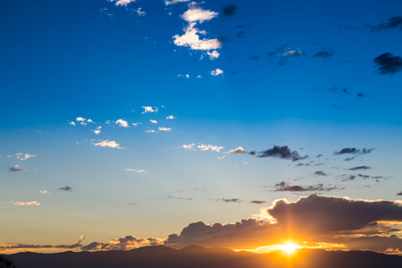 blue sky: Scenic view of a beautiful sunset with blue sky and clouds over the mountains