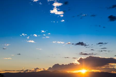 cielo azul: Vista panorámica de una hermosa puesta de sol con cielo azul y las nubes sobre las montañas