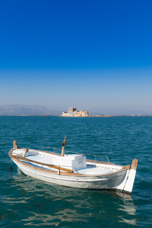 nafplio: Seascape with fishing boat and Bourtzi castle in background, Nafplio, Greece Stock Photo