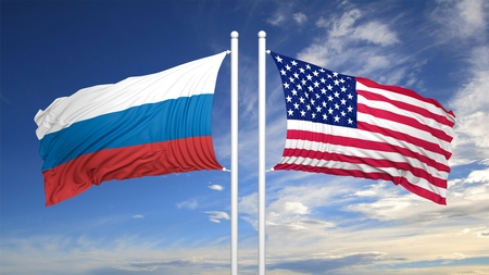 flagpole: American and Russian flags against of blue sky