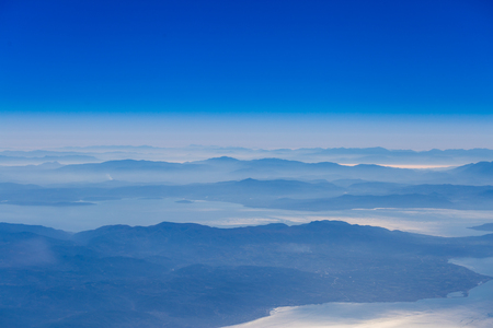 jet plane: Deep blue sky above landscape with mountains and sea,atmospheric aerial photography Stock Photo