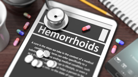 hemorrhoids: Tablet with Hemorrhoids on screen, stethoscope, pills and objects on wooden desktop.