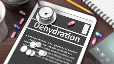 dehydration: Tablet with Dehydration on screen, stethoscope, pills and objects on wooden desktop. Stock Photo