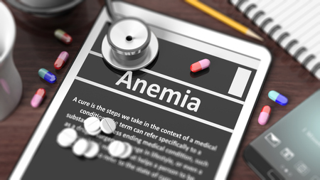 anemia: Tablet with Anemia on screen, stethoscope, pills and objects on wooden desktop. Stock Photo